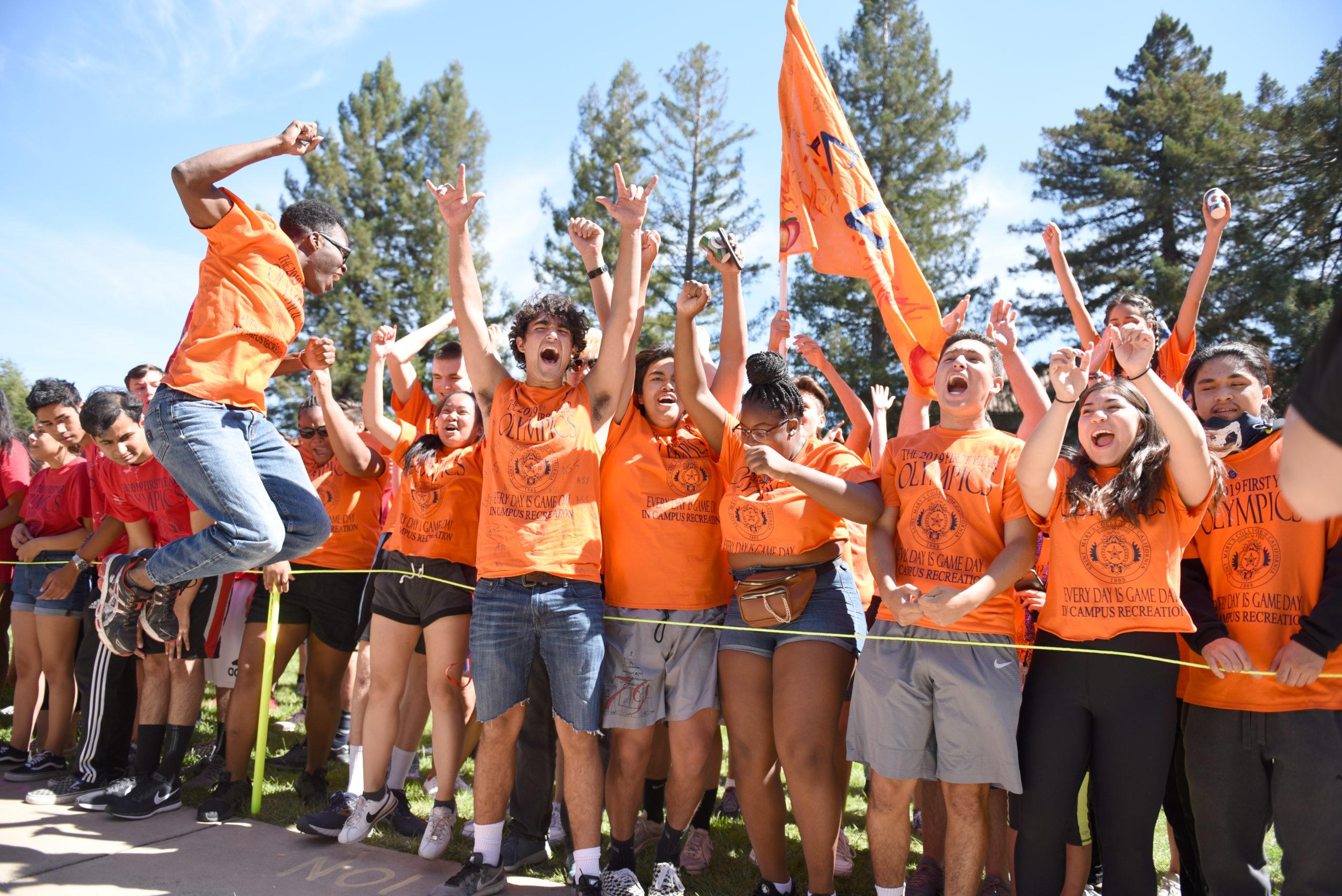 Students wearing orange shirts representing their dorm cheering on De La Salle Lawn