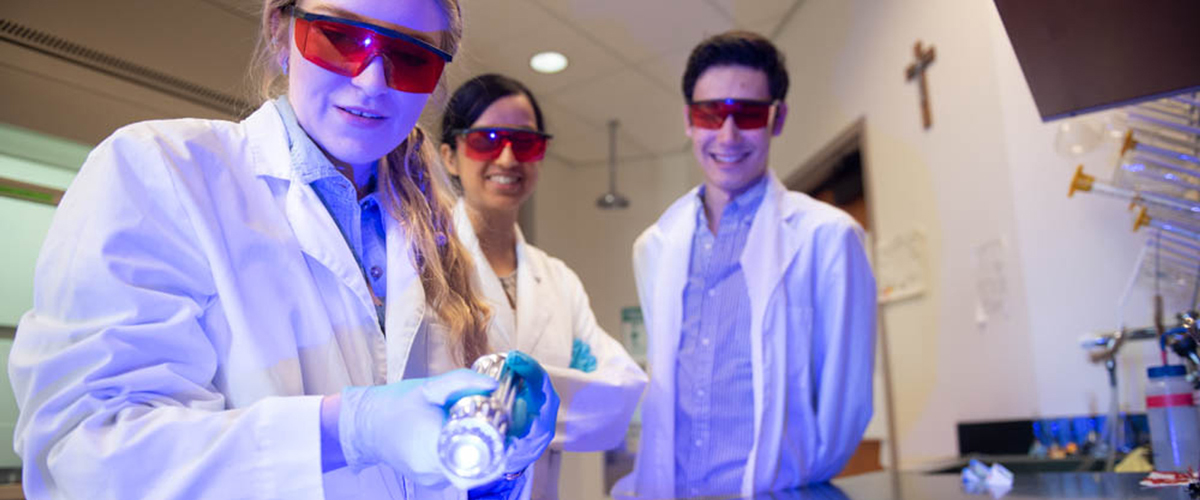 A student in a lab wearing red glasses while holding a laser shining blue light at a table and two others standing behind her smiling