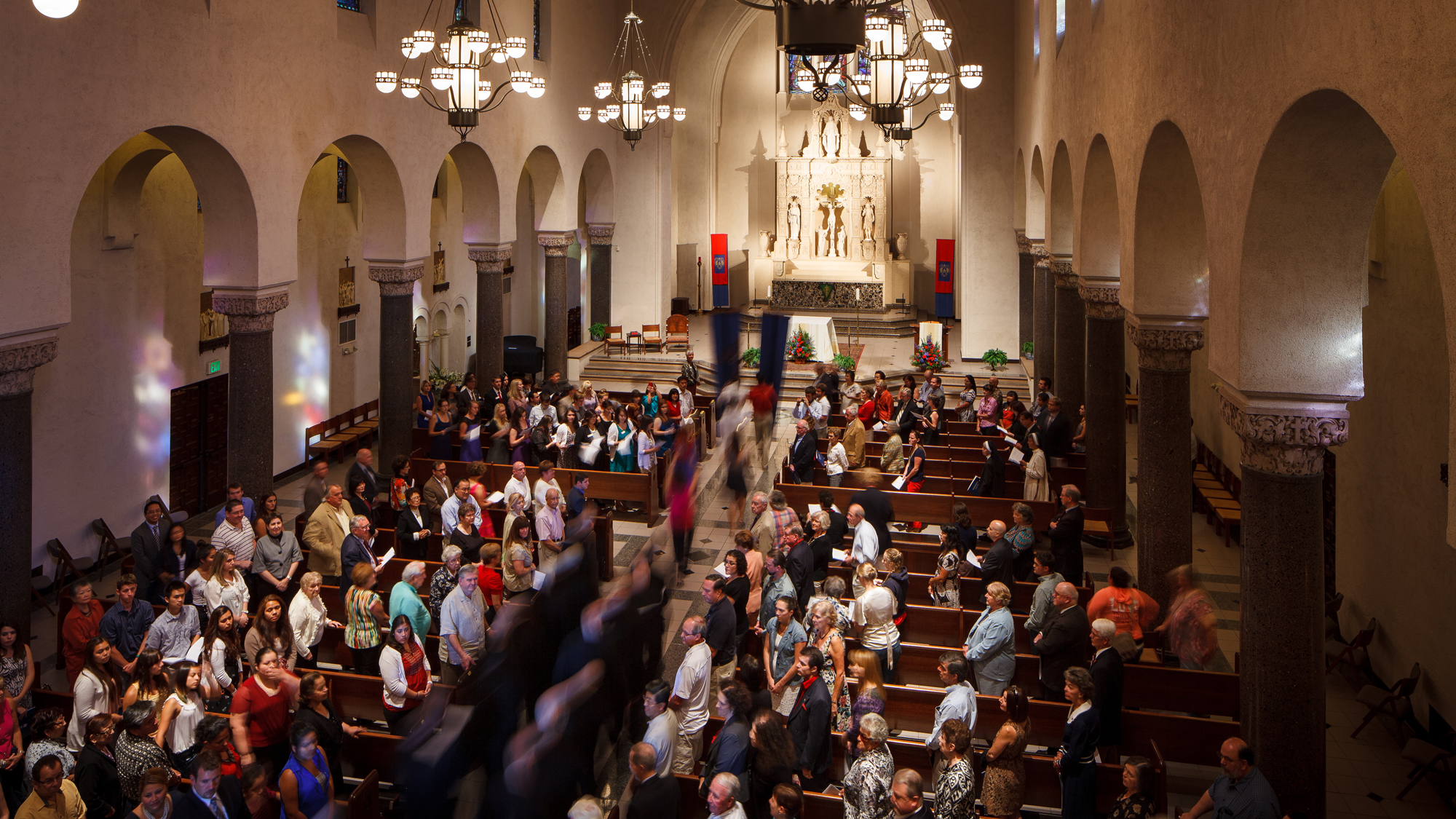 A procession moving down the aisle of the chapel with people in the pews standing up and watching