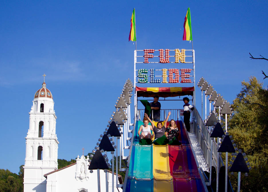 Students with their arms up sliding down a large slide during a carnival on chapel lawn