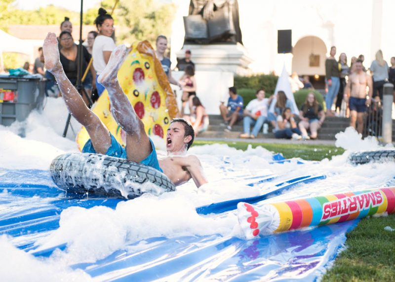 A student leaning back yelling on an inflated pool toy sliding down a foam slip and slide