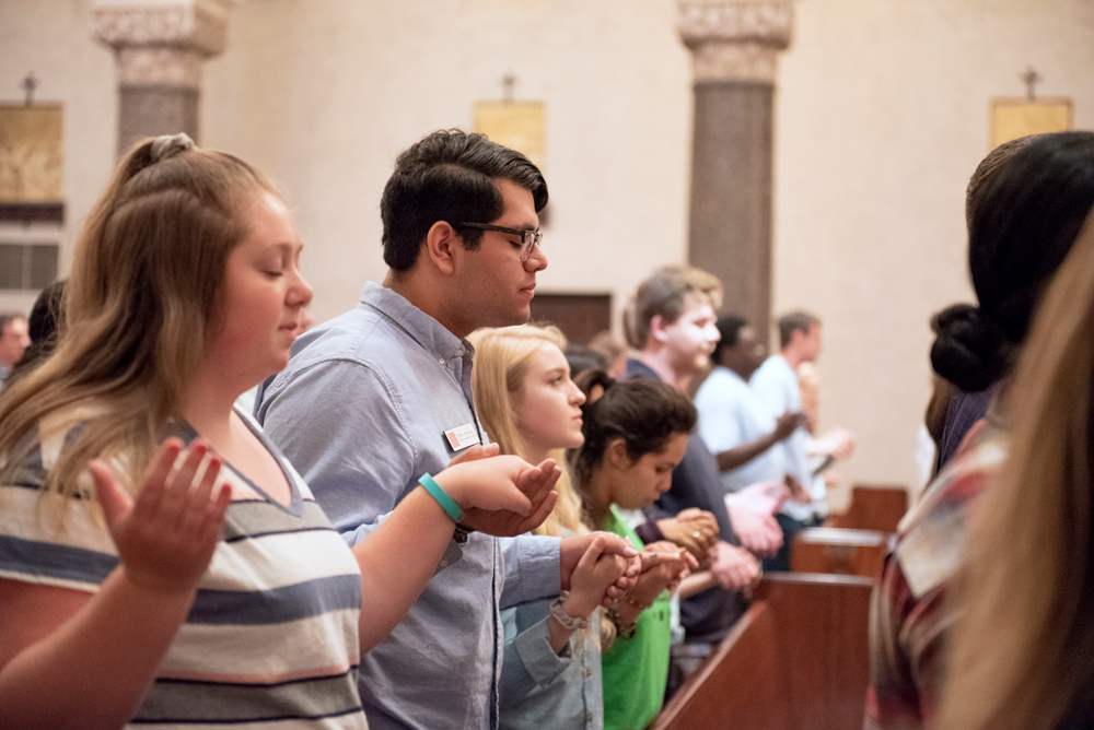 Students standing in the pews of the chapel holding hands with their eyes closed