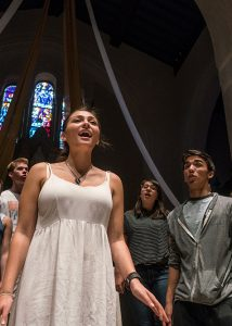 A girl singing during a choir performance in the chapel
