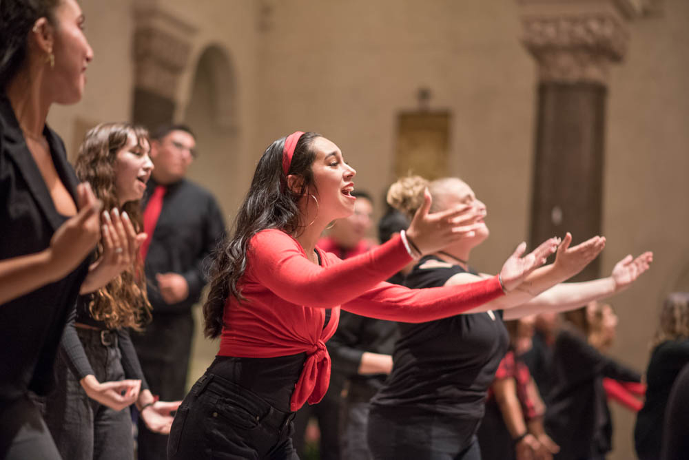 A girl leaning forward with her arms out singing during a choir performance in the chapel