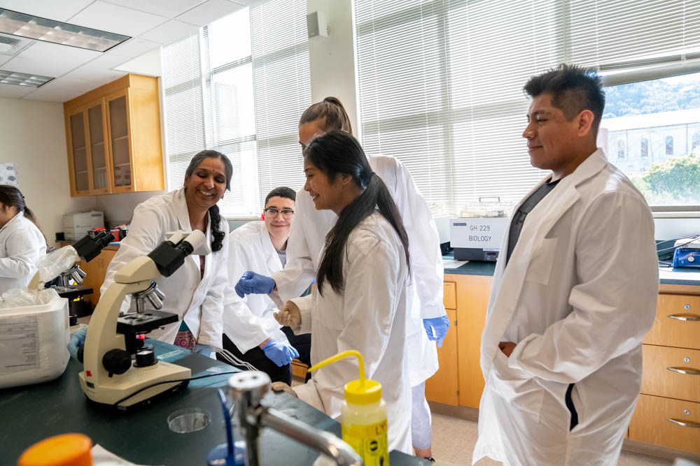 Student's in lab coats standing around a professor adjusting a microscope