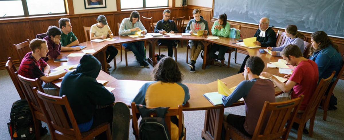 Students looking at books while sitting around a round table in seminar class