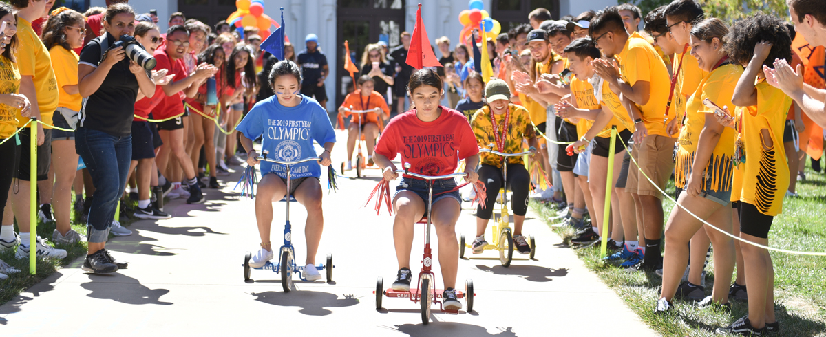 Students racing on tricycles with students on either side cheering on De La Salle Lawn