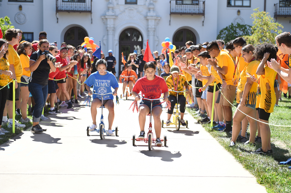 Students on tricycles racing in the first year olympics with other students cheering on the side lines