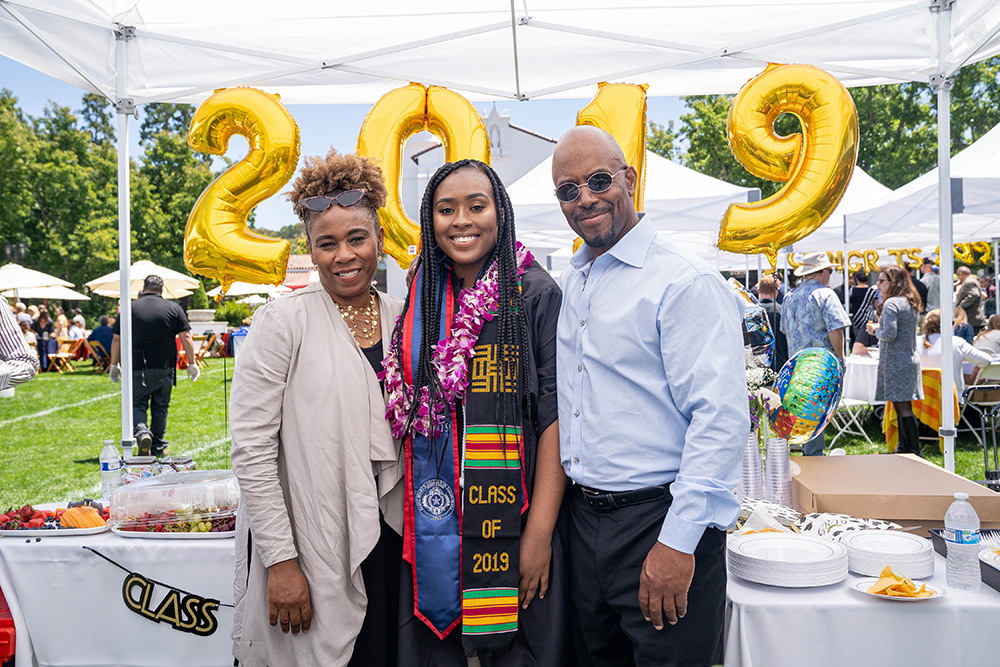 A female graduate smiling at the camera with her parents on either side and a 2019 inflatable balloon sign behind her