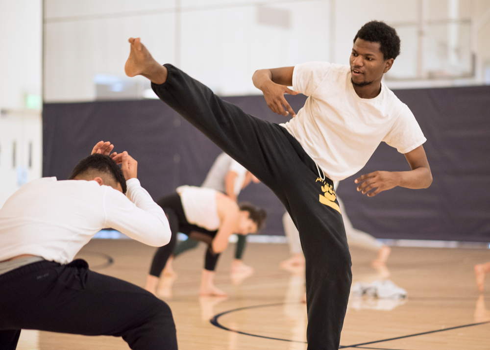 A student doing a high kick in a class about Capoeira during Jan Term