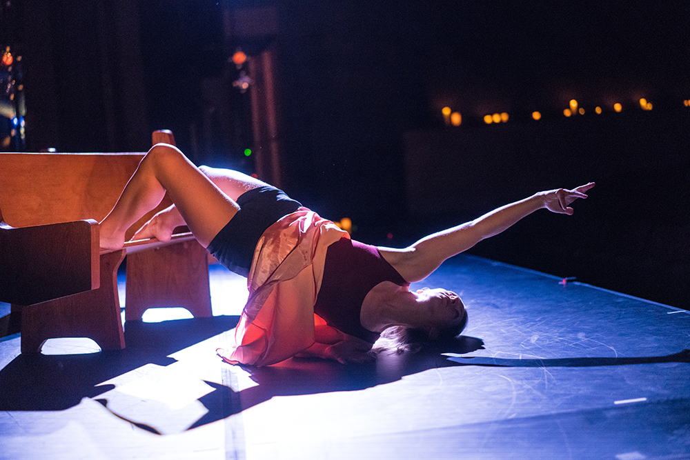 A dancer stretched out on the ground during a performance on the stage of LeFevre Theatre