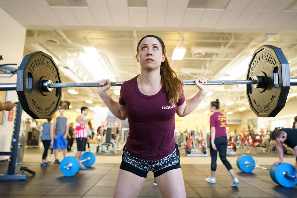 A girl in the middle of a deadlift, looking up, with weights behind her head