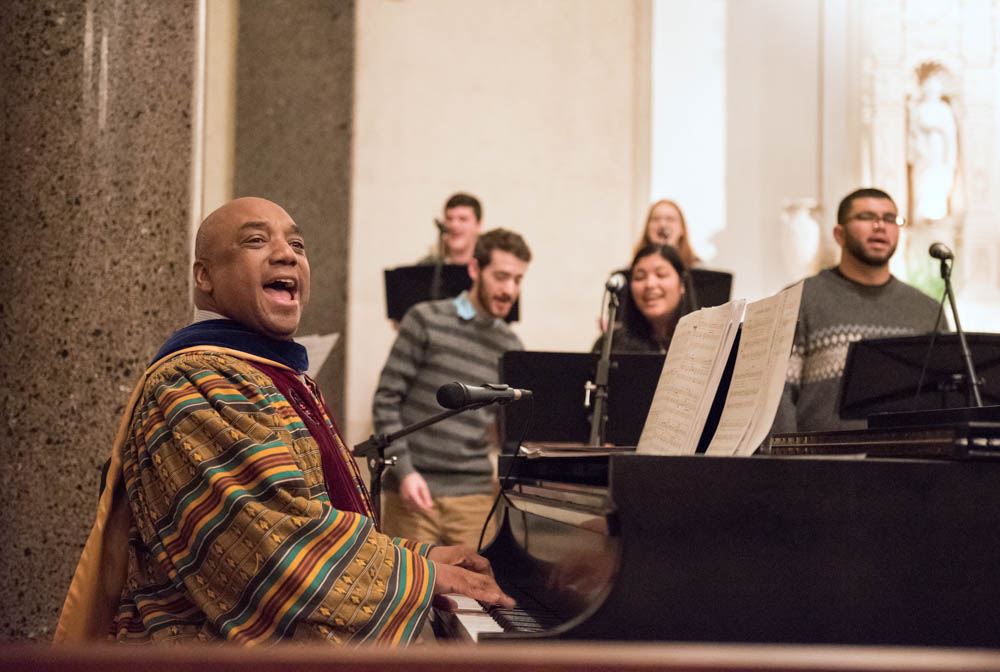A man smiling while playing a piano and singing during mass