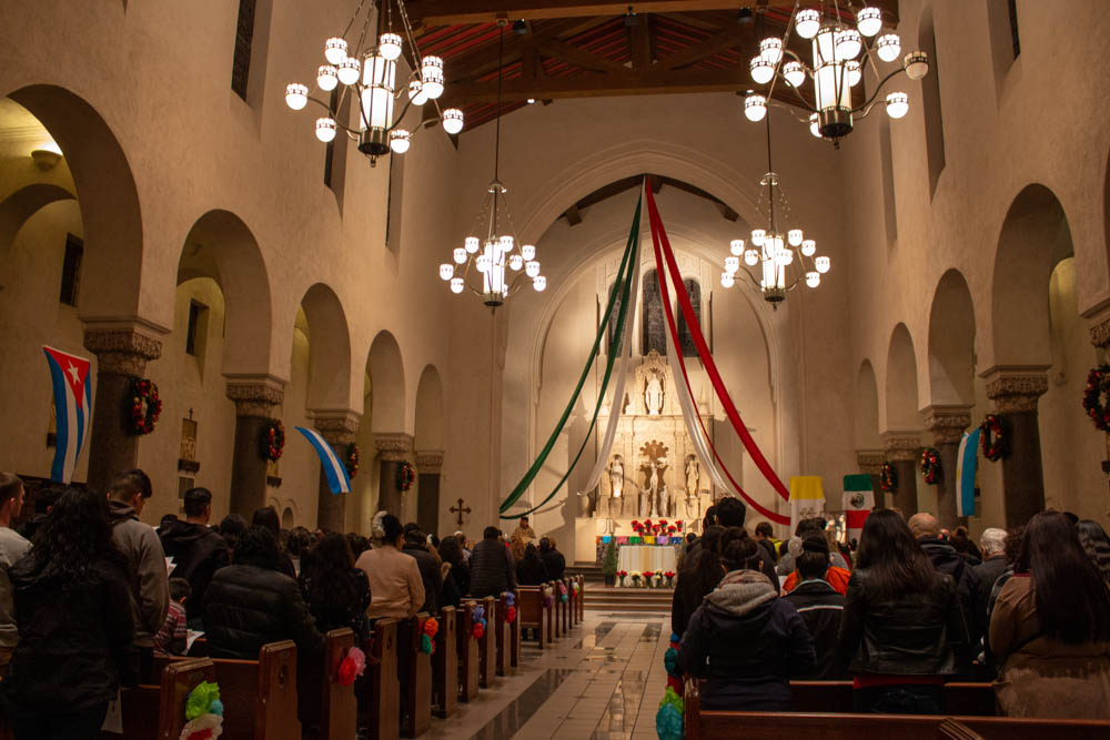 A mass in the chapel with green, red, and white garlands hanging from the front