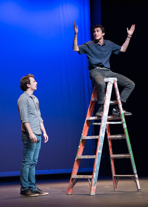 Actor sitting on a ladder with his arms up and another actor looking at him from below while on stage