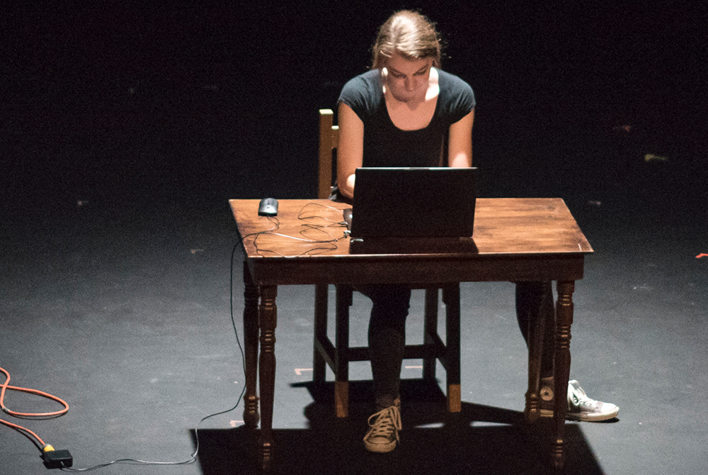 An actress performing her own play while sitting at a desk with a computer during a performance on stage of LeFevre Theatre