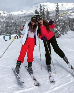 Two Girls leaning their heads together and yelling while on skis with snow covered mountains behind them