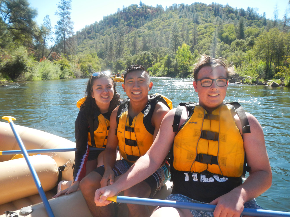 Three students with life jackets on, smiling at the camera, while sitting on a raft in a river