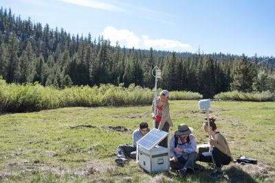 students and a professor out in the wilderness conducting an experiment with solar panels