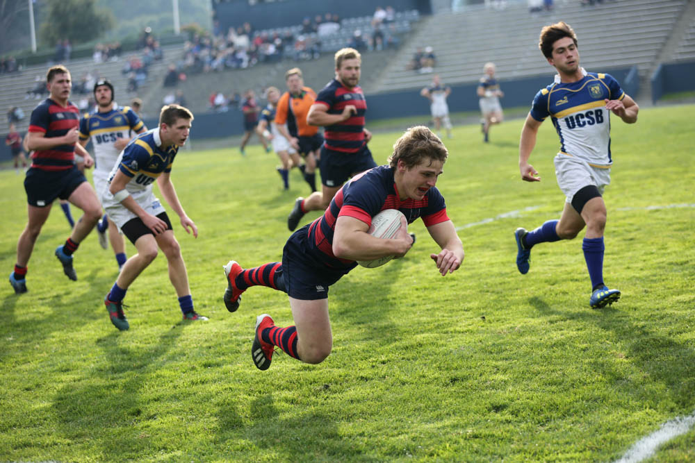 A boy diving forward with a rugby ball under his arm and guys running behind him