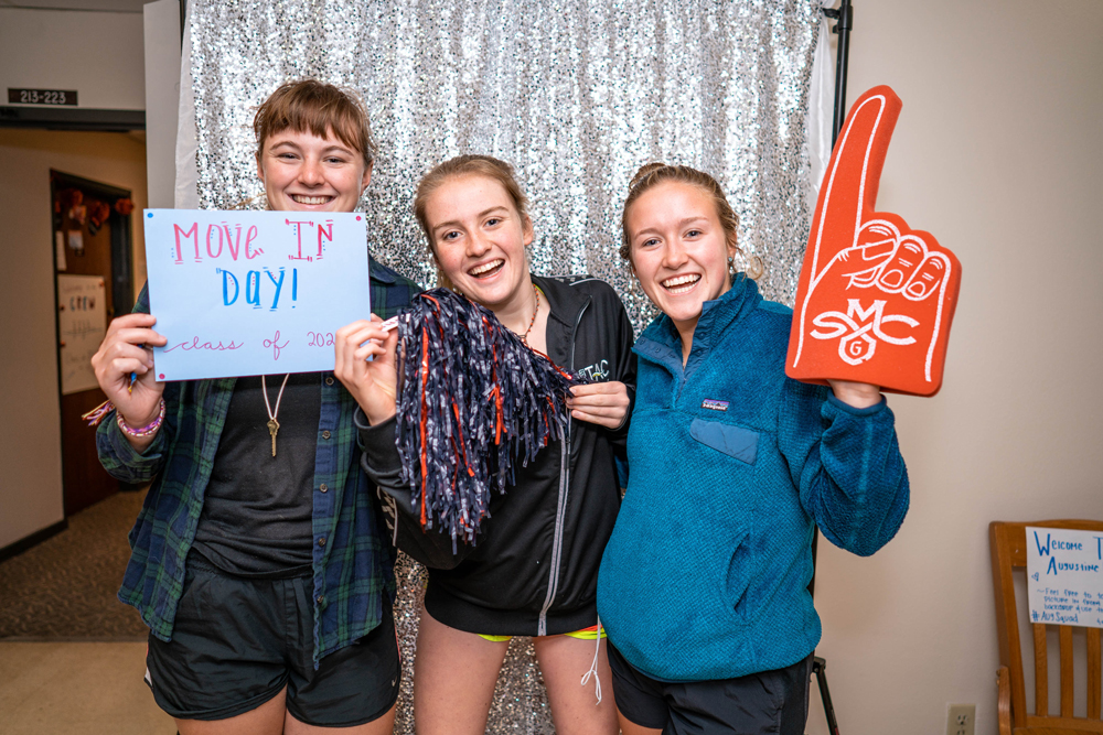 Three girls smiling in front of a glitter background. One is holding a Move In Day sign, one has a pom pom, and one has a big finger with the Gael's logo on in