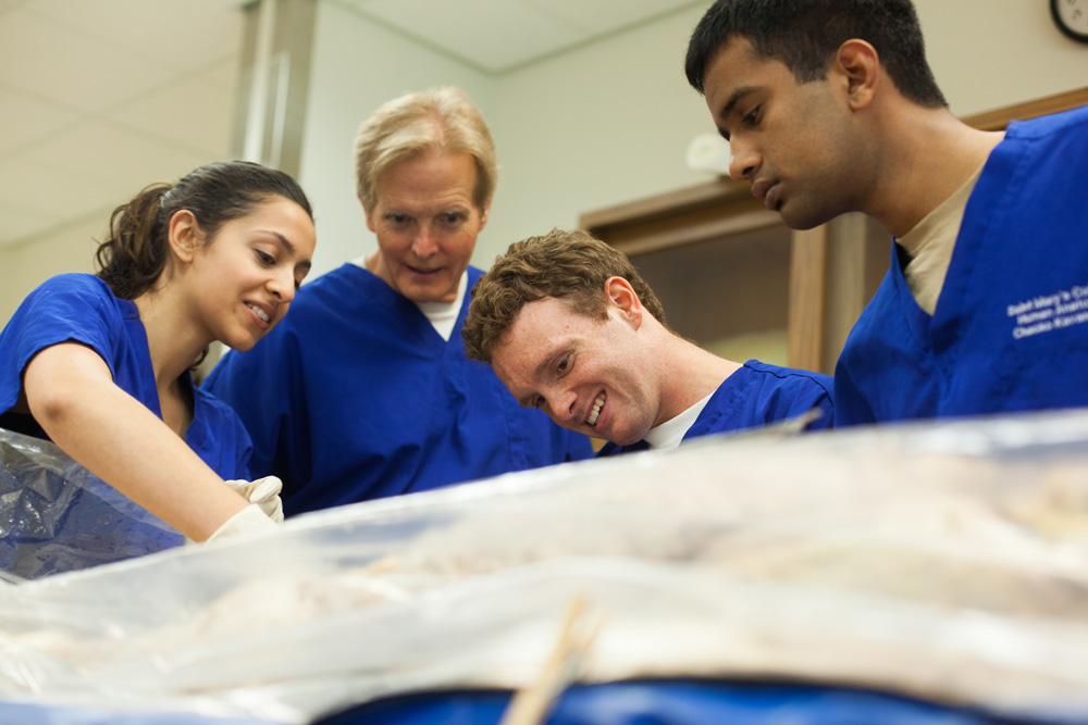 Shows students and a professor looking at a cadaver under a tarp