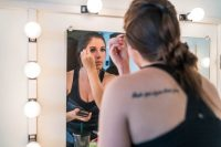 An actress looking in the mirror putting on makeup back stage of LeFevre Theatre