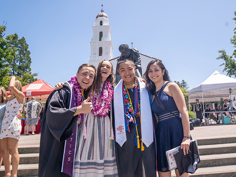 Four students with graduation gowns smiling in front of the chapel lawn
