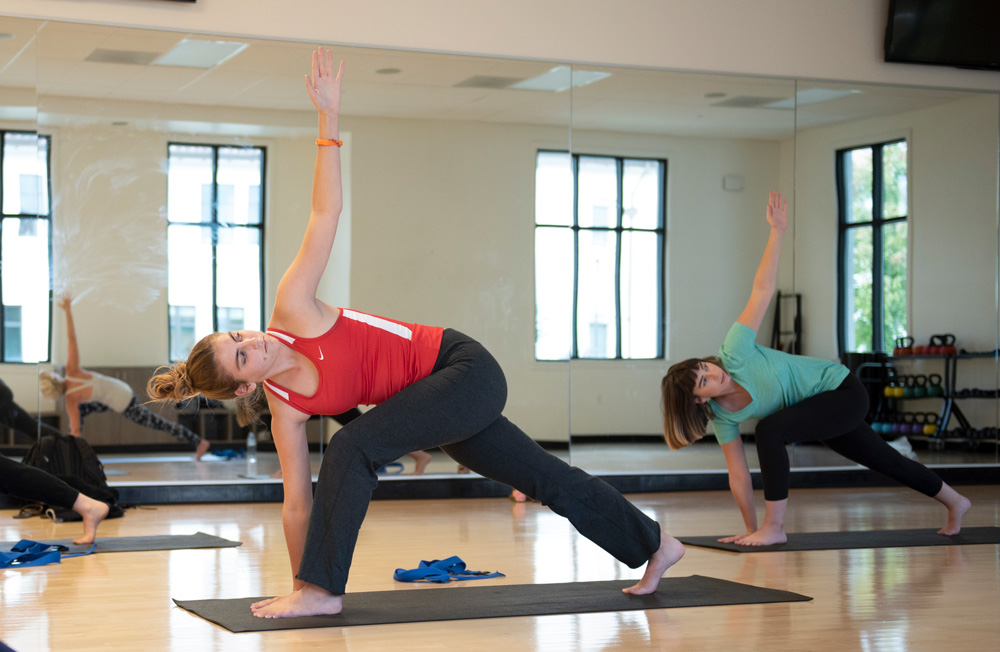 Students leaning down with left arm up during a yoga class